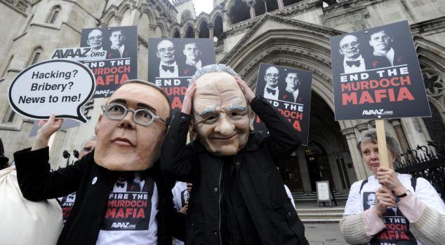 Demonstrators dressed as James and Rupert Murdoch protest outside the High Court in London