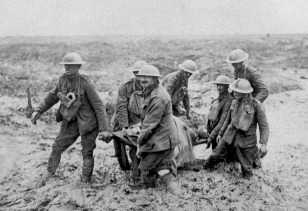 A stretcher patrol of British soldiers struggle to move forward in the knee deep mud of the trenches. (historyboomers.blogspot.com)