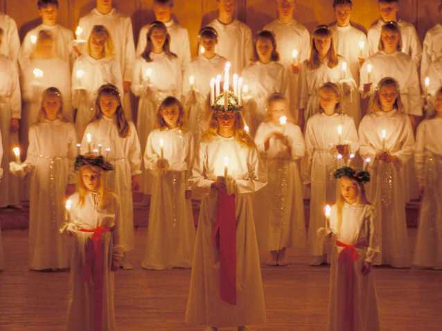 """Saint Lucy's feast day of December 13th is mostly spent in darkness in Scandinavia due to the day being so short as the Winter Solstice approaches. Traditionally on Lucy's feast day, Swedish girls will dress all in white and wear head pieces consisting of the 4 candles of Advent topped off with a central candle rising above symbolizing Lucy's """"Light"""" with everything being lit aflame! If having your eyes gouged out isn't enough for all you religious masochists, then how about putting your cranium at risk by torching your entire head on fire."""