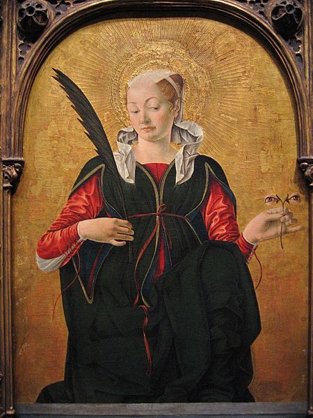 Santa Lucia or Saint Lucy by Francesco della Cossa, 1475. Rather than hold her jelly ball sight organs in her hand, this image has Saint Lucy daintily holding her eyeballs between her thumb and index finger as if they were on a flower stem.